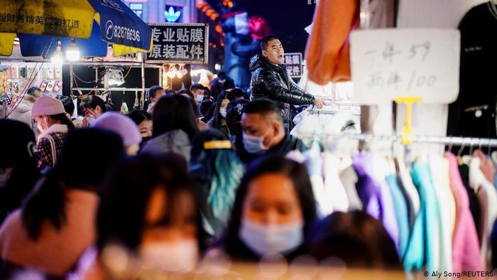 Люди в масках на уличном рынке в Ухане