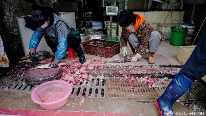 Люди чистят и разделывают рыбу прямо на полу и дренажных решетках на рынке