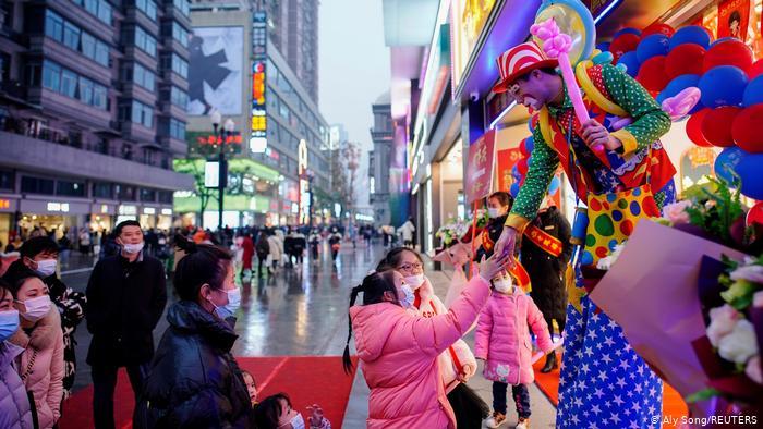 Девочка пожимает руку клоуну на одной из улиц Уханя