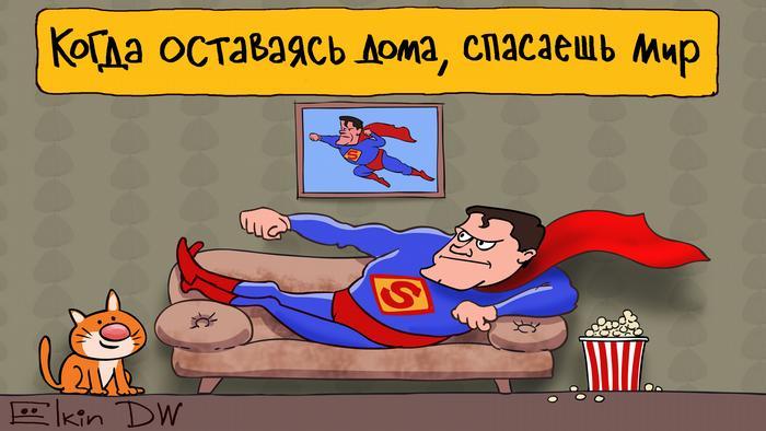 Мужчина в костюме Супермена лежит на диване, а над ним висит плакат Когда оставаясь дома, спасаешь мир