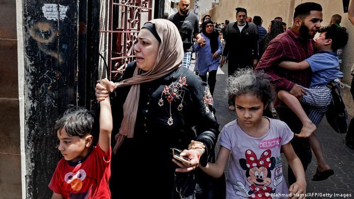 Женщины, дети и мужчины спасаются бегством. Город Газа в секторе Газа.