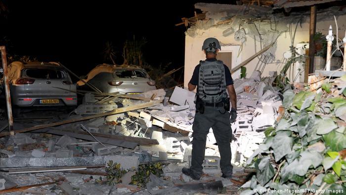 Сотрудник спецслужб Израиля обследует руины дома в городе Йехуд