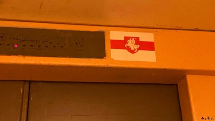 наклейка на входе в лифт - бело-красно-белый флаг