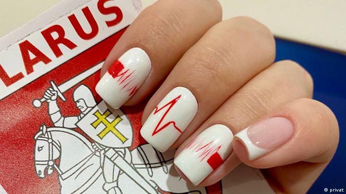 Пальцы руки, ногти которых выкрашены в белы и красный цвета