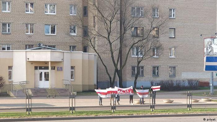 цепь солидарности в Минске - люди стоят с бело-красно-белым флагом