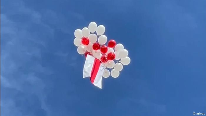 Бело-красно-белый флаг в небе, прикрепленный к белым и красным воздушным шарам