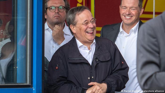 Кандидат в канцлеры Германии Армин Лашет смеется на встрече с людьми, пострадавшими от наводнения