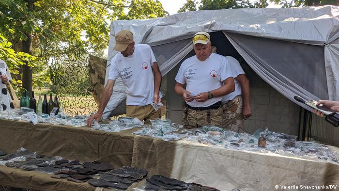 на столах лежат предметы, найденные в массовом захоронении жертв репрессий в Одессе