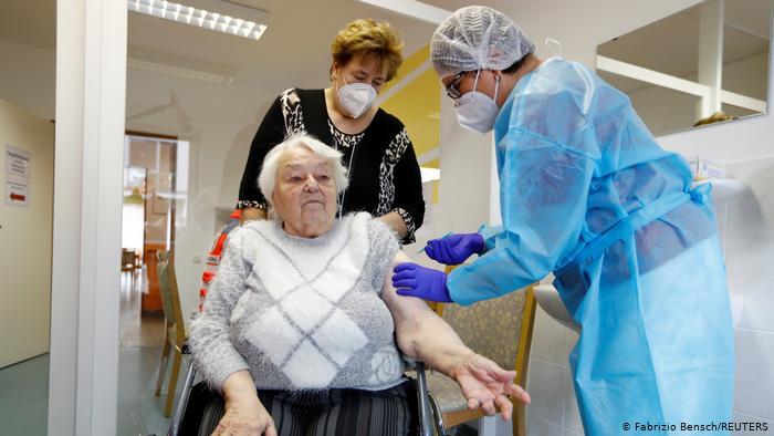 Пожилой немке делают прививку вакциной BioNTech и Pfizer