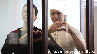 Мария Колесникова и Максим Знак в зале суда показывают руками сердечки