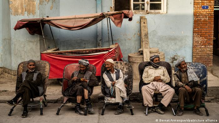 Мужчины сидят на стульях на обочине дороги